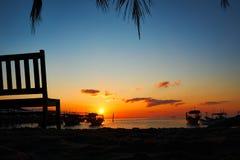 De bank met mooie zonsopgang op achtergrond op tropische strandkoh rong modelleert met longtailboten terwijl de zon gaat stock foto