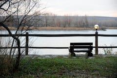 De bank is plaats voor eenzaamheid over de rivier Stock Foto's