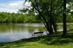 De bank van het park bij het meer. Stock Foto