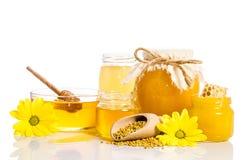 De bank van honing met honingraten, glaskom met honing Stock Afbeelding