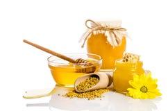 De bank van honing met honingraten, glaskom met honing Royalty-vrije Stock Afbeelding