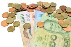 De bankbiljetten en de muntstukken van Thailand op wit worden geïsoleerd dat stock foto