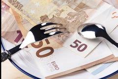 De bankbiljetten 50 en 10 euro zijn in een witte plaat met een blauwe grens Bovenop hen zijn een vork en een lepel royalty-vrije stock fotografie