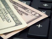 De bankbiljetten van Amerikaanse dollars zijn op een calculator Stock Foto's