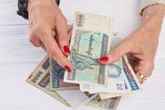 De bankbiljetten van Birma in Kaukasische vrouwenhanden Royalty-vrije Stock Afbeelding