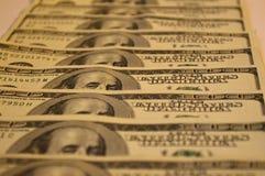 De bankbiljetten van dollars worden op een rij gestapeld Stock Afbeelding