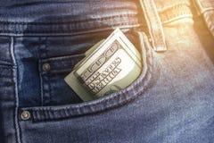 De bankbiljetten van honderden Amerikaanse dollars zijn verdraaid in een buis, die uit een zak van jeans plakken Amerikaanse munt Stock Foto's
