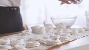 De banketbakker bestrooit gepoederde suiker op heemst Kokslagen van heemst met de gepoederde suiker stock footage