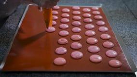 De banketbakker met gebakjespuit doet koekjes dezelfde grootte vóór het bakken in de keuken Ruw dessert op dek Keuken stock video