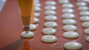 De banketbakker met gebakjespuit doet koekjes dezelfde grootte vóór het bakken in de keuken Ruw dessert op dek Keuken stock footage