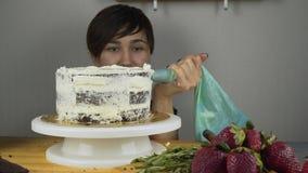 De banketbakker verfraait de cake en behandelt het met boterroom Banketbakkerijhulpmiddelen: spatel voor groeperingsroom stock video