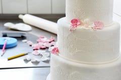 De banketbakker verfraait huwelijkscake in bakkerij stock afbeelding