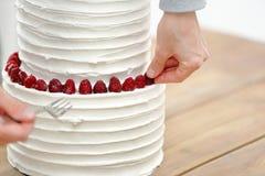 De banketbakker verfraait witte huwelijkscake stock foto's