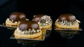 De banketbakkershand bracht het gebakjedessert aan van de rij Frans minidiemousse met chocoladeglans wordt behandeld stock videobeelden
