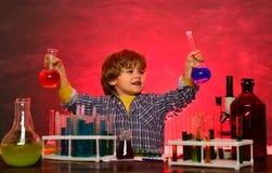 De bar ut ett nytt experiment i kemi Hem- skolg?ng Lycklig liten forskare som g?r experiment med provr?ret royaltyfri foto