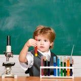 De bar ut ett nytt experiment i kemi Ungen l?r i grupp p? bakgrund av svart tavla Deltagaren av den h?ga gruppen f?r de f?rsta ku royaltyfria foton