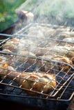 De barbecue rookte kippenbenen voorbereidingen treffend bij de metaalgrill bij openlucht, selectieve nadruk stock afbeeldingen