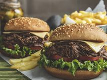 De barbecue trok rundvleeshamburger, sandwich, frieten, saus, donker bier, graan op een houten dienblad stock afbeelding