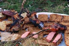 De barbecue van het straatvoedsel Geroosterde worsten met brood op de brand stock foto