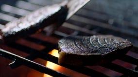 De barbecuepartij, sluit omhoog van lapjes vlees bij de grill met brandvlammen, draait de chef-kok hen over, langzame motie stock footage