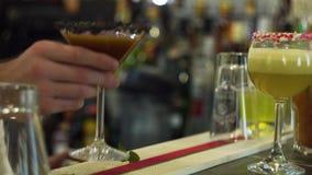 De barman dient een gele cocktail Bar tegen, cocktailminnaars stock video