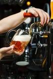 De barman giet bier in een glasdrinkbeker van de kraan royalty-vrije stock foto