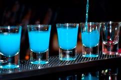 De barman giet blauwe alcoholische drank in kleine glazen op bar Stock Afbeelding