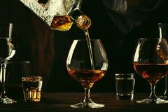 De barman giet de cognac of de brandewijn in groot wijnglas op de oude barteller Uitstekende houten achtergrond in bar of bar, na royalty-vrije stock foto's