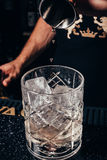 De barman giet de alcohol in een oud manierglas Stock Afbeeldingen