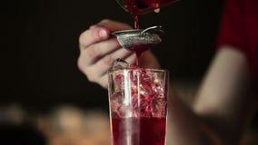 De barman giet de inhoud van het glas stock videobeelden