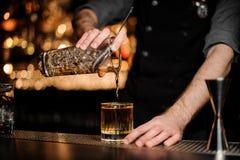 De barman giet een alcoholcocktail toevoegend whisky royalty-vrije stock fotografie
