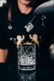 De barman giet het ijs in oud manierglas Royalty-vrije Stock Fotografie