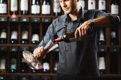 De barman giet rode wijn in transparant schip in kelder royalty-vrije stock fotografie