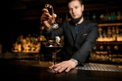 De barman laat vallen ijsblokje in alcoholcocktail stock foto's