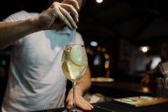 De barman maakt een alcoholische sprankelende zoete cocktail bij de bar Alcoholische dranken bij de bar of de nachtclub Het leven stock afbeelding
