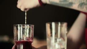 De barman mengt de inhoud van het glas stock videobeelden