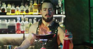 De barman met een baard bereidt een heerlijke cocktail op een rond gasfornuis voor stock videobeelden