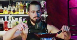 De barman met een baard bereidt een heerlijke cocktail op een rond gasfornuis voor stock video