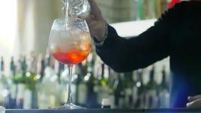 De barman op het werk maakt verfrissende drank en voegt mineraal sodawater aan wijnglas met ijs en cognac toe stock videobeelden