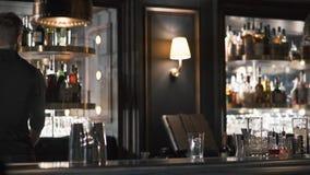De barman rolt de ronde plank kiezend noodzakelijke fles alcohol Barman die cocktail in moderne bar met flessen maken stock video