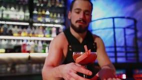 De barman stelt de gebeëindigde cocktail op en dient op de camera stock video