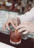 De barman verfraait drank met citroenschil Royalty-vrije Stock Afbeelding