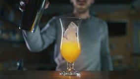 De barman voegt ijs aan de cocktail toe en vult glas met gemengde alcohol in langzame motie, die cocktails in een bar, alcohol ma stock video