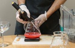 De barman voegt soda aan een drank toe Stock Afbeelding