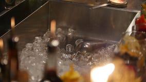 De barman werpt ijs in een gootsteen in de bar door kaarslicht wordt verlicht dat stock videobeelden