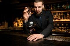 De barman zet ijsblokje in alcoholcocktail stock afbeelding