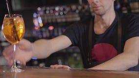 De barman zet twee zwart stro in hoog cocktailglas met ijsblokjes en oranje dichte omhooggaand De jonge mens bereidde smakelijk v stock video