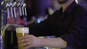 De barwerknemer overhandigt klant een groot glas vers bier met schuimend wit schuim stock footage