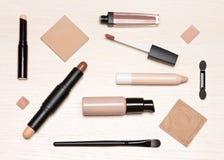 De basismake-upcosmetischee producten op lichte houten lijstvlakte lagen stock afbeeldingen