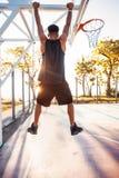 De basketbalspeler hangt op de rand sportuitrusting, sportcompetities Royalty-vrije Stock Afbeeldingen